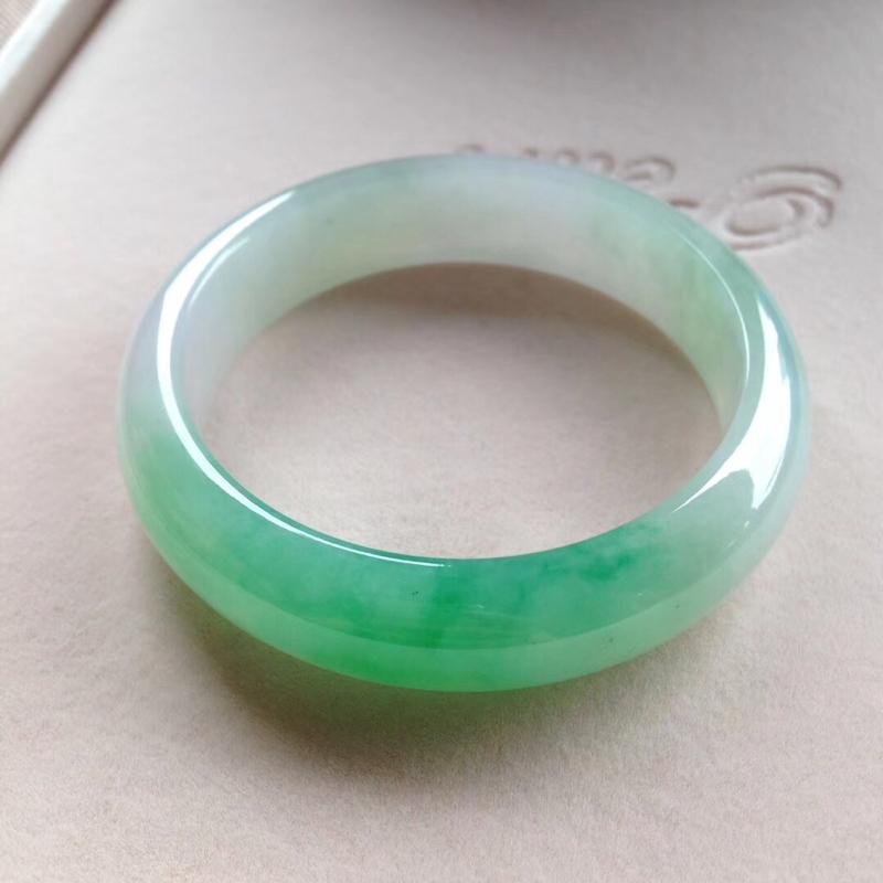 飘阳绿正圈镯,尺寸56*14.5*8.5 完美细腻,版型宽厚,通透水润,一截翠色灵动鲜辣,非常惹眼!