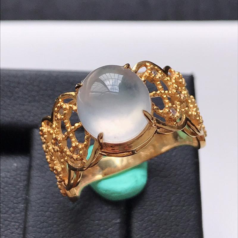 天然翡翠A货。冰种白冰蛋面戒指。圈口:17mm。18K金镶嵌伴钻。冰润通透,款式新颖,品相极佳。镶金