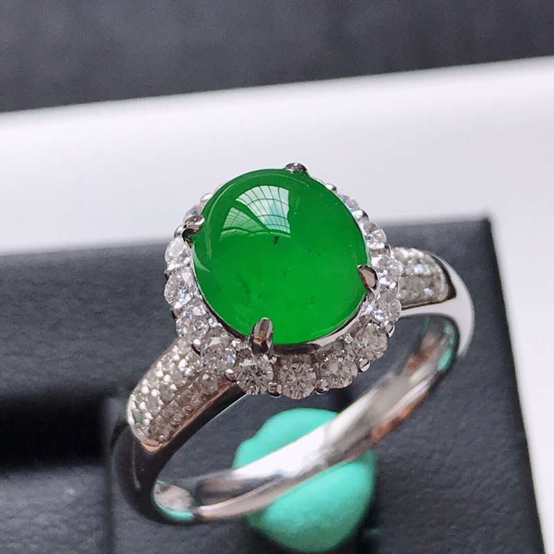 天然翡翠A货。冰种阳绿蛋面戒指。圈口:17mm。18K金镶嵌伴钻。色泽鲜艳,品相极佳。镶金尺寸:11