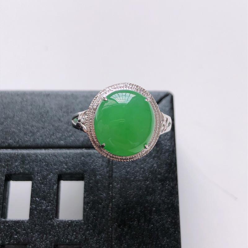 天然翡翠A货。冰糯种满绿蛋面戒指。圈口:17mm。18K金镶嵌伴钻。水润通透,色泽鲜艳。镶金尺寸:1