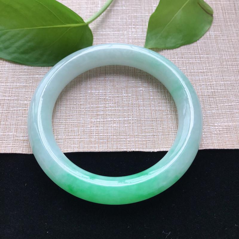 圆条:56。天然翡翠A货。糯化种飘绿圆条手镯。色泽鲜艳,佩戴清秀优雅。尺寸:56*10.6mm