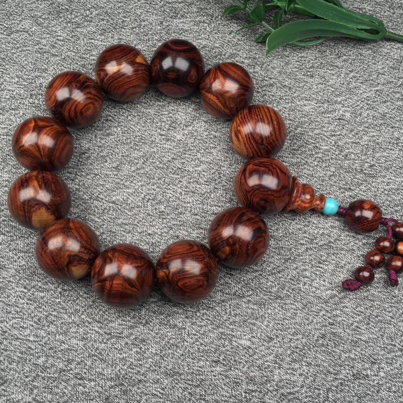 海南黄花梨紫红油梨对眼,鬼脸X纹纹理。规格是:高20mmX12颗,重:47.4克。紫红底色,大小黑线